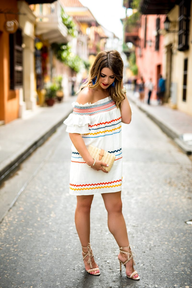 the streets of cartagena red carter off the shoulder dress dress in cartagena off the shoulder dress striped dress vacation dress what to wear on vacation travel to cartagena the beautiful steets of cartagena red yellow and blue dress straw clutch what to do in cartagena