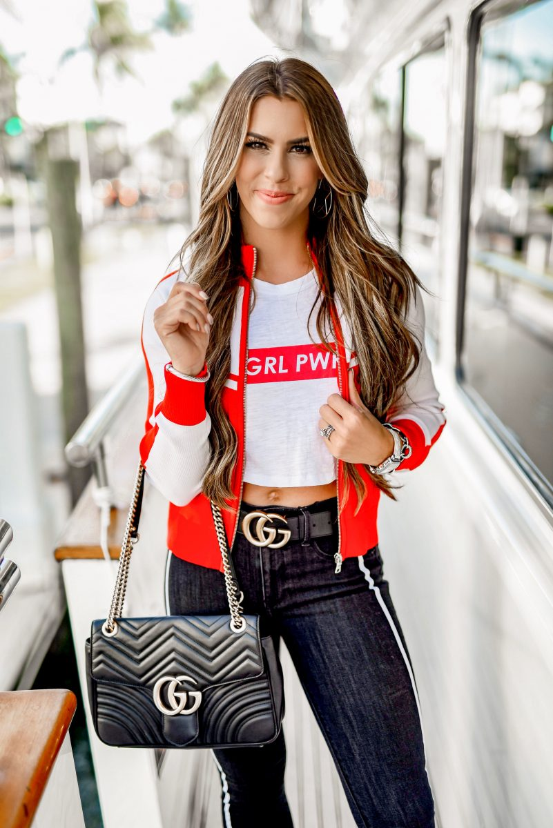 Olivia culpo express collection the new Olivia culpo clothing collection at express track jacket red jacket black skinny jeans side stripe girl power cropped tee red track jacket sporty fashion edgy fashion gucci belt and gucci bag Olivia culpo style